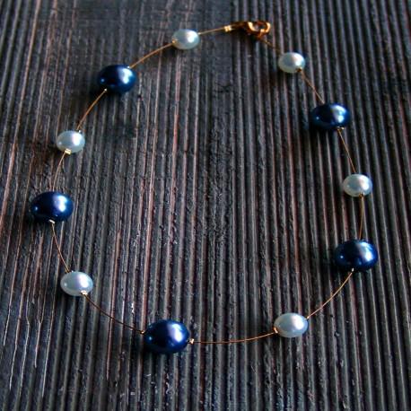 Ketting met witte- en antracietkleurige glasparels op gouddraad